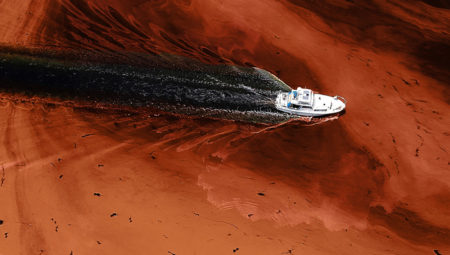 photo of boat floating in red tide water.